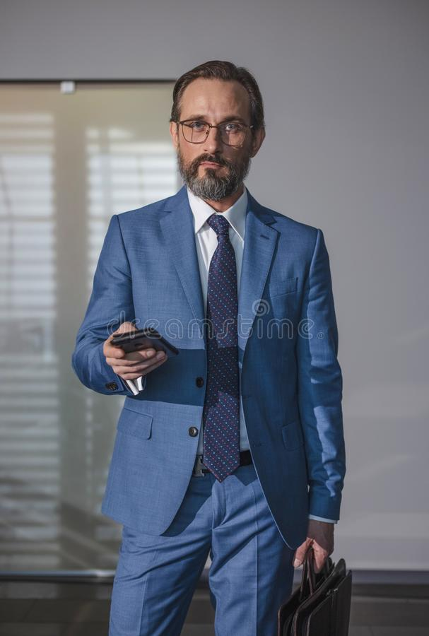 Aged professional man using smart phone in office building indoors. Businessman holding mobile smartphone using app texting sms royalty free stock photos
