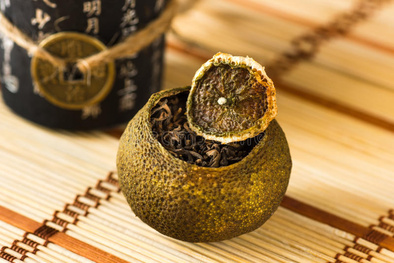 Aged pu-erh tea in a dry tangerine peel on a chinese style straw mat, selective focus royalty free stock images