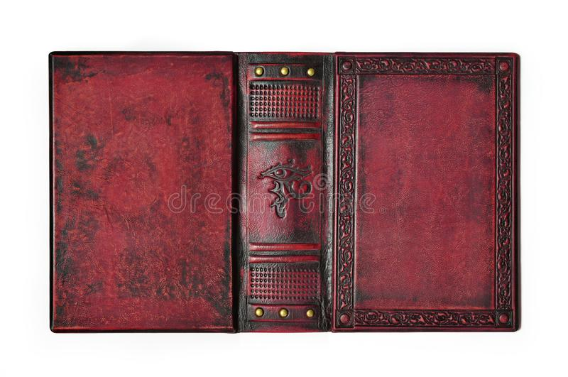 Aged red leather book cover with the embossed ancient Egyptian symbol `The Eye of Horus` lay down to the table opened. And isolated royalty free stock photography