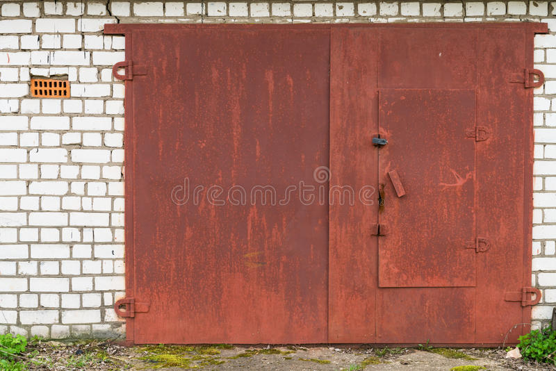 Aged red metal garage gate. Aged closed red metal garage gate on white brick wall stock photo