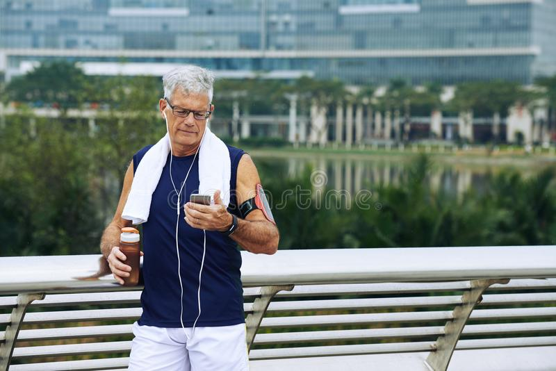 Aged runner checking phone royalty free stock images