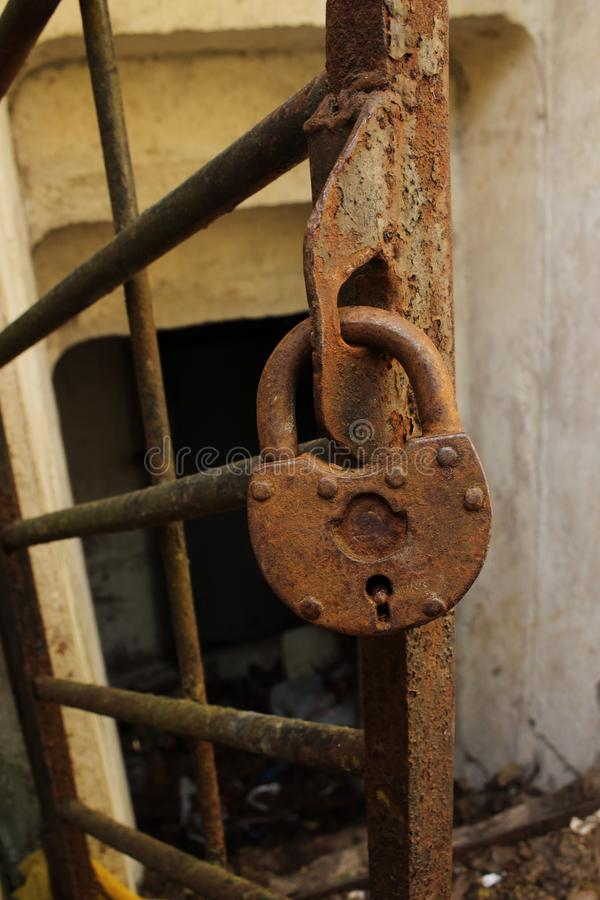 Aged rusty metal padlock hanging on metal bar gate to bomb shelter stock photography