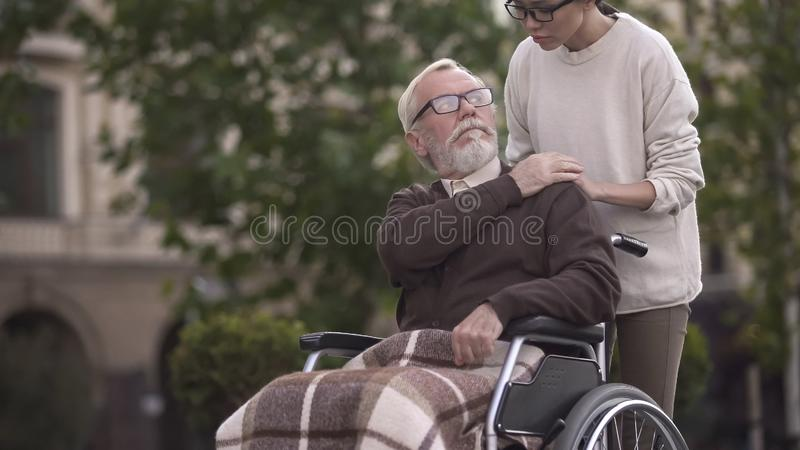 Aged sad disabled male in wheelchair covering young lady hand, family support royalty free stock photos