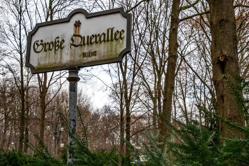 Aged signpost in Tiergarten park of Berlin Germany. Old rusty sign with inscription of street name `Grobe Duerallee` in gothic. Tiergarten public park of Berlin royalty free stock image