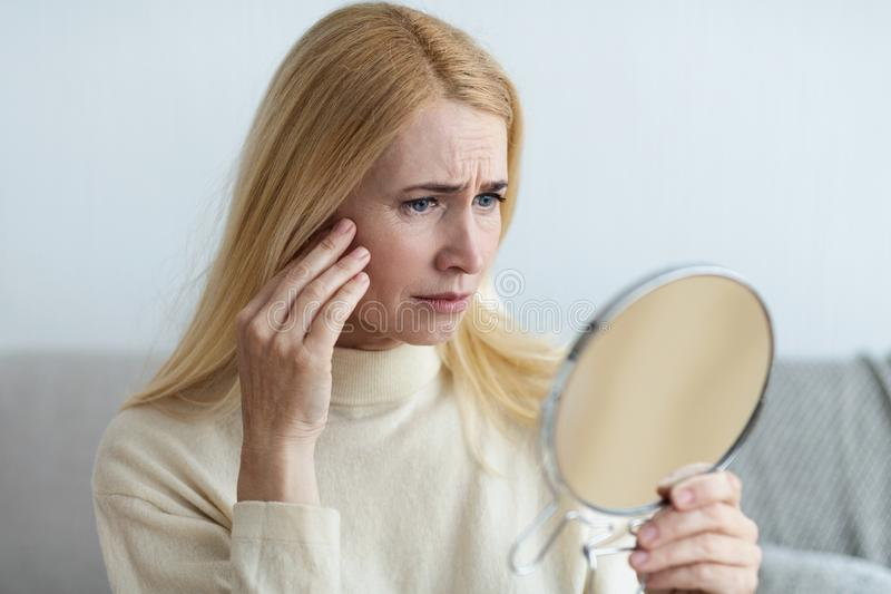 Mature Sad Woman Looking At Wrinkles In Mirror royalty free stock photos