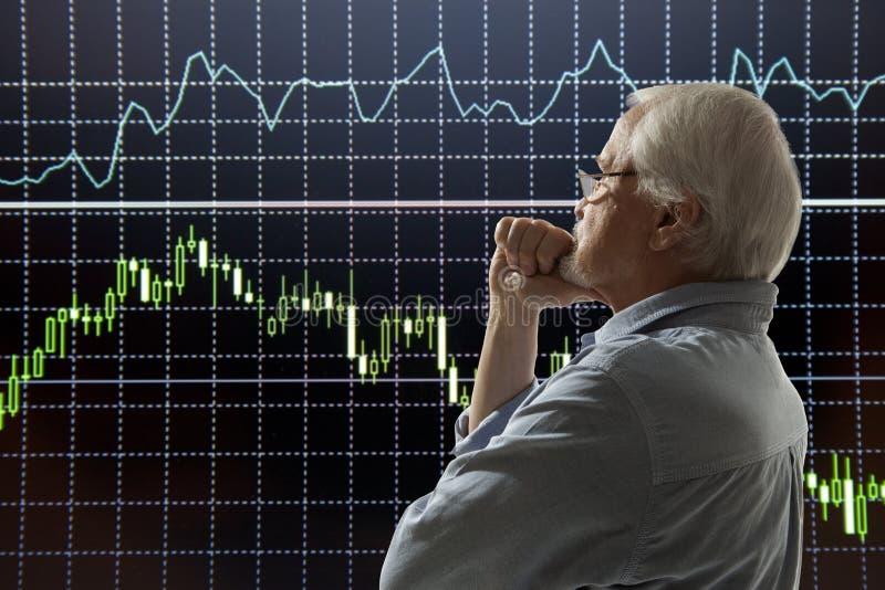 Aged stock trader. Looking at monitors royalty free stock photo