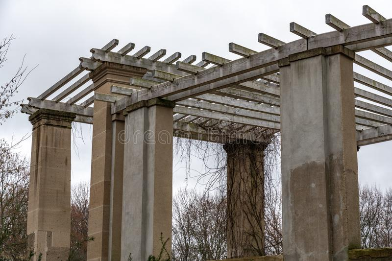 Classical architecture style arbor in Tiergarten park of Berlin Germany. Aged stone columns of ancient arbor with striped wooden roof. Garden house overgrown royalty free stock image