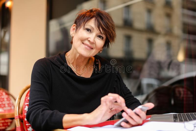 aged female teacher working in open air with laptop and wri stock photo