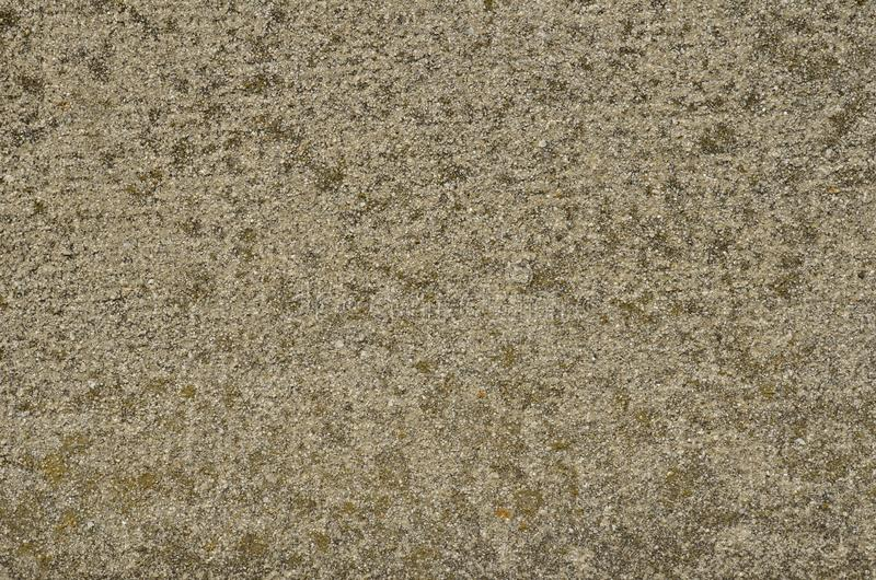 Aged textured surface of the artificial stone material. Seasoned textured surface of an artificial stone made of mixture of mortar and tiny pieces of white stock image