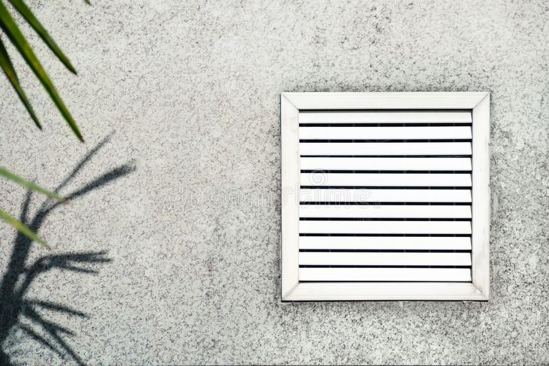 Aged vent with white shutters on the background of gray concrete under leaves of the palm. royalty free stock photography