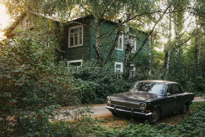 Aged vintage soviet black retro car on background of green wooden old house and autumn park stock photos