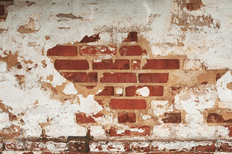 Aged weathered brick wall with cracked stucco. Old grunge stone texture. Aged weathered brick wall with cracked stucco. Grunge background stock photography