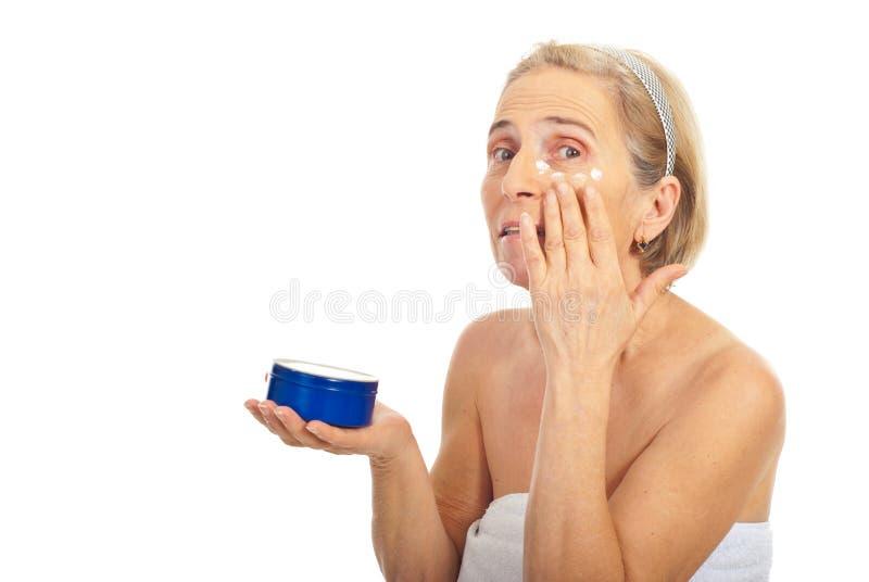 Aged woman apply cream around eye royalty free stock photo