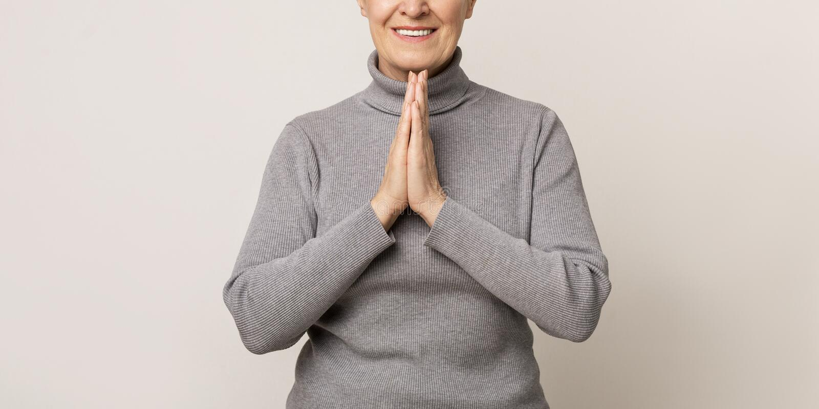 Aged woman with clasped hands, pleading or appealing for something. royalty free stock photos