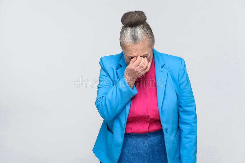 Aged woman cry and have bad mood. Aged woman cry with bad mood. Emotion and feelings concept. Portrait of expressive grandmother with light blue suit standing stock photography