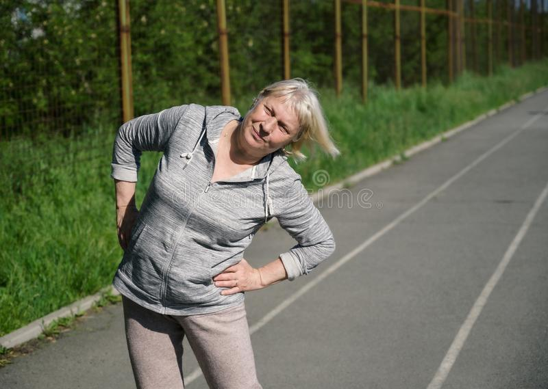 Aged woman doing exercises. stock photo
