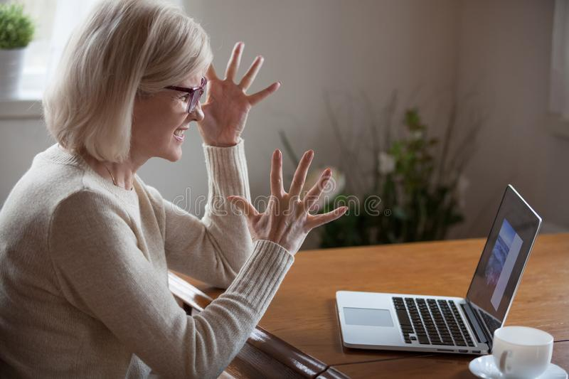 Angry middle aged woman having difficulties with computer. Aged woman in glasses sitting at table looking at computer screen feeling irritation and anger by stock photos