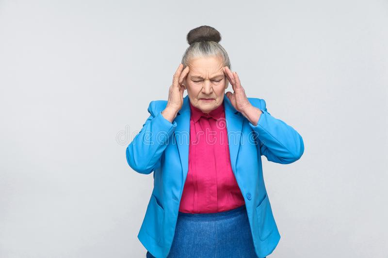 Aged woman have migraine and headache pain. Portrai of expressive grandmother with light blue suit and pink shirt standing with collected bun gray hair. Studio stock photo