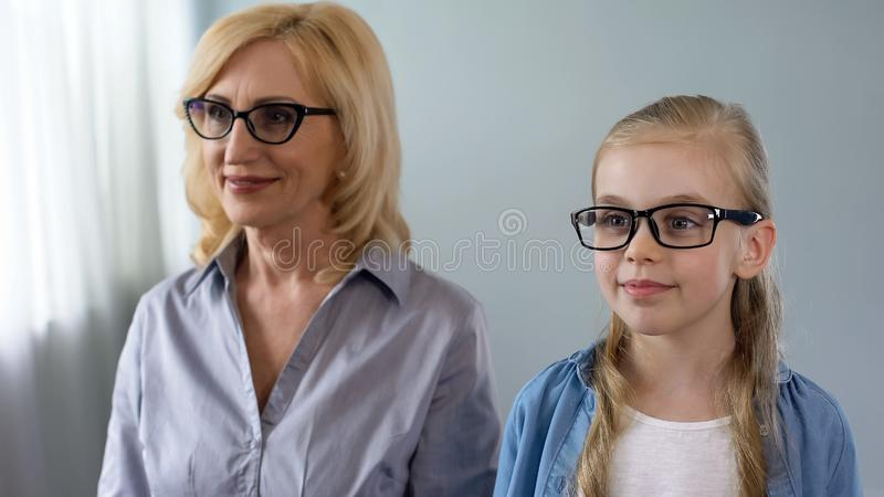 Aged woman and her little granddaughter visiting eyes specialist, health care. Stock photo royalty free stock photography