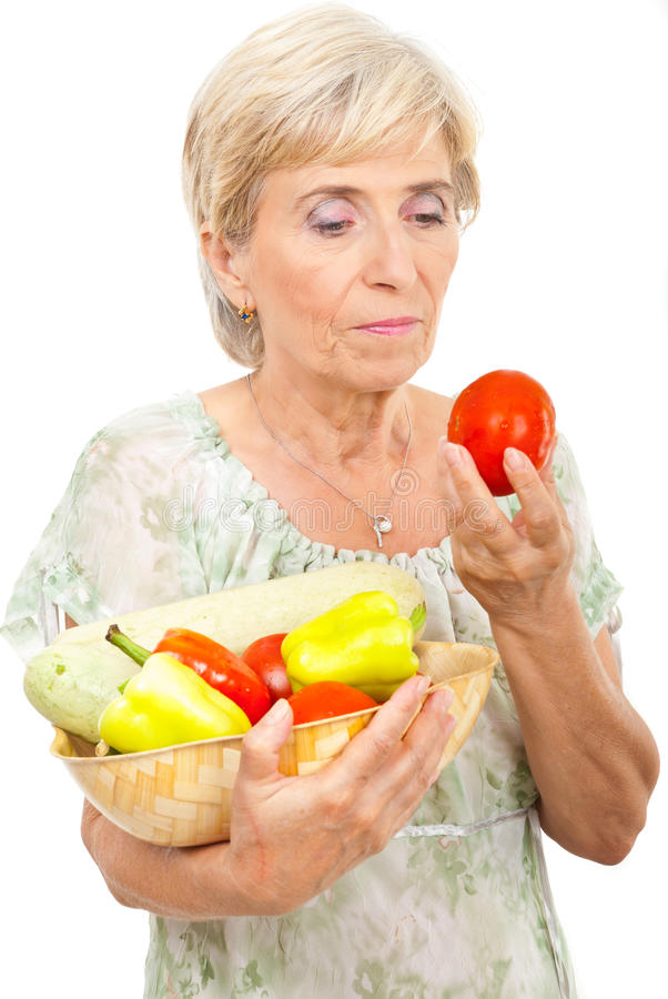 Aged woman holding vegetables stock photography
