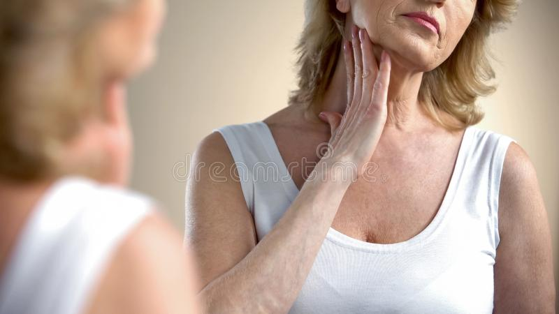 Aged woman looking in mirror at wrinkled skin, thinking about plastic surgery royalty free stock photos