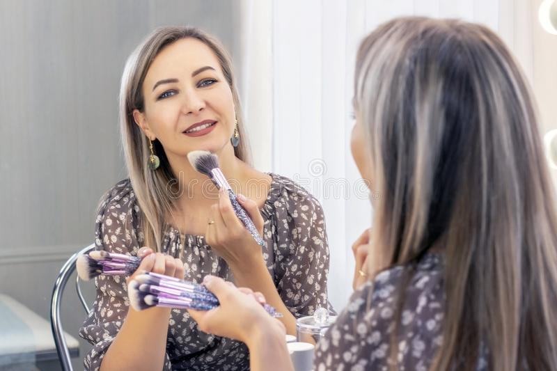 Aged woman puts on her makeup. looking in the mirror. myself a makeup artist. applying powder on the face with a large brush stock image
