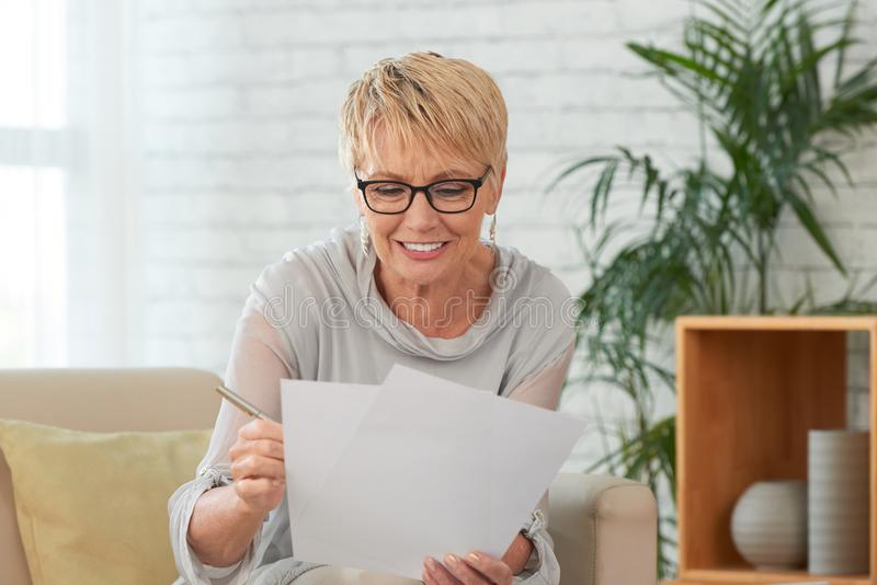 Aged woman reading document royalty free stock images