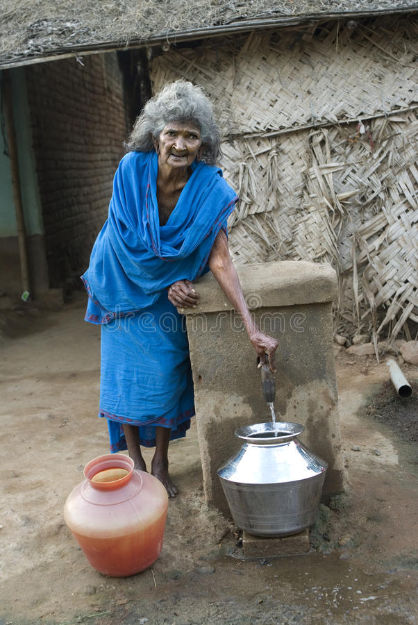 Aged woman taking drinking water from public tap. Drinking water- Aged lady taking drinking water from the public tap near her home for her domestic use stock photography