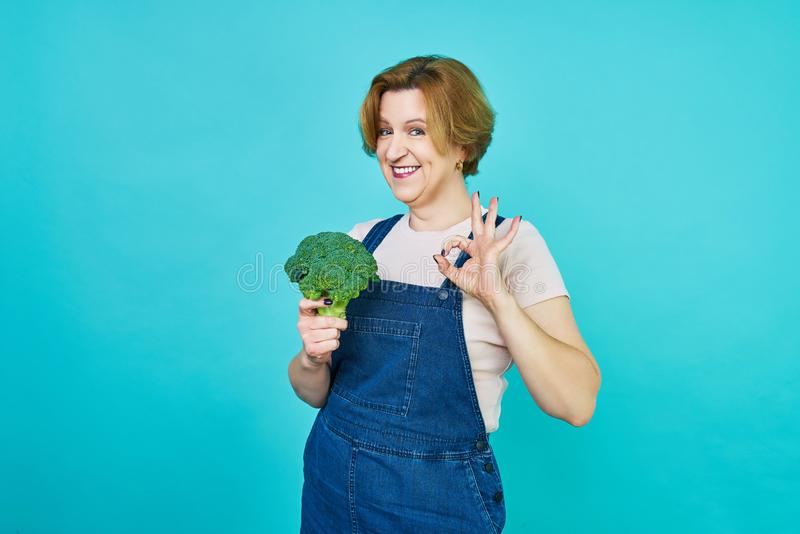 An aged woman is about to eat a vegetarian dish. Funny old woman on a broccoli diet. Healthy eating concept. royalty free stock images