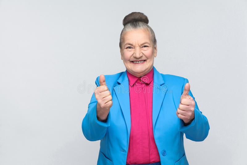 Aged woman toothy smiling and showing like sign. Aged woman toothy smiling with like sign. Emotion and feelings concept. expressive grandmother with light blue royalty free stock image
