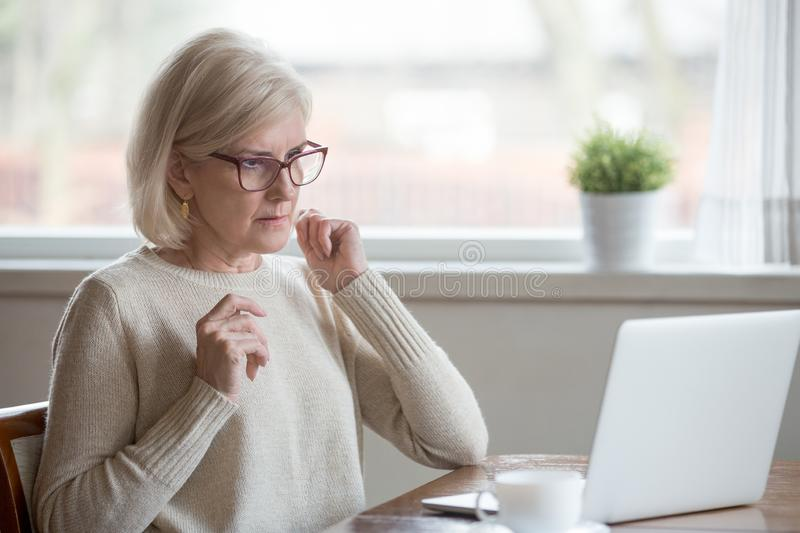 Aged woman using laptop confused seeing error message. Surprised aged woman using laptop worried seeing error message on screen, concerned senior female get royalty free stock photos