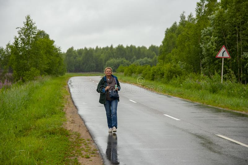 An aged woman walks along a wet highway that is in the woods stock photography