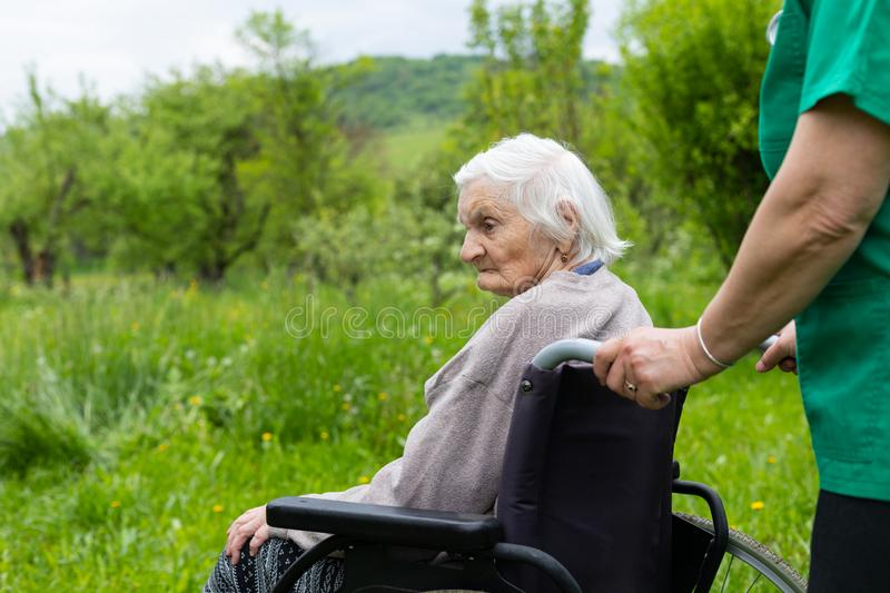 Aged woman in a wheelchair with medical assistance. Aged woman with dementia sitting in a wheelchair royalty free stock photo