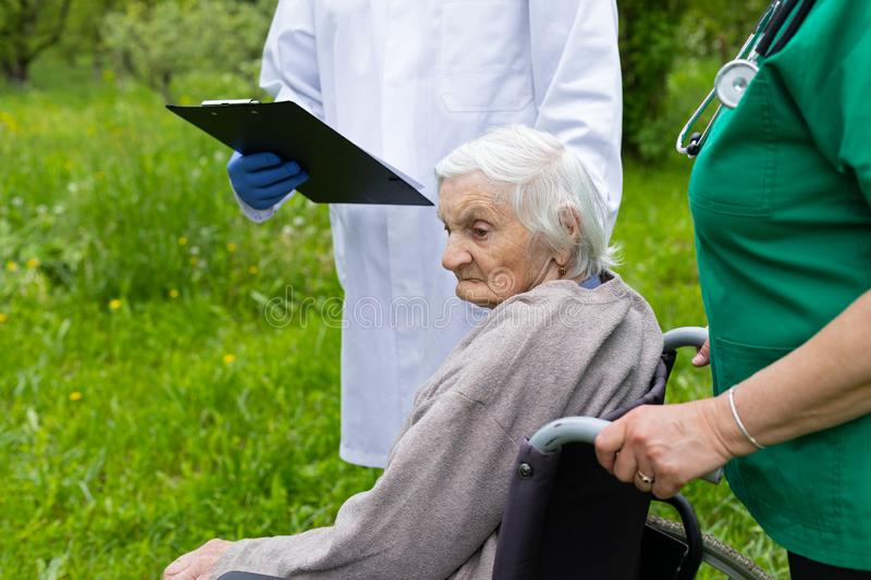 Aged woman in a wheelchair with medical assistance. Aged woman with dementia sitting in a wheelchair stock images