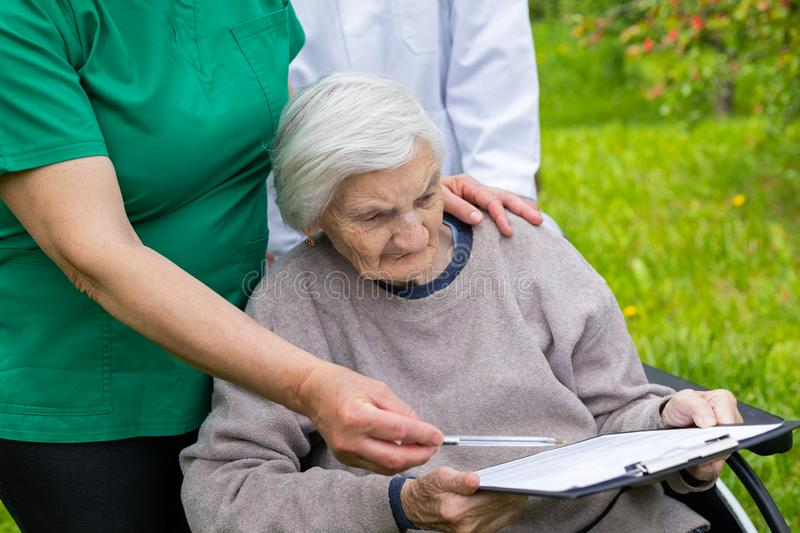 Aged woman in a wheelchair with medical assistance. Aged woman with dementia sitting in a wheelchair, male doctor and female nurse taking care of her outdoor royalty free stock images