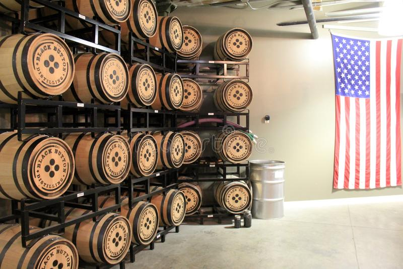 Aged wood barrels stacked on metal shelving units, Black Button Distillery, Rochester, New York, 2017. Rows of aged wood barrels stored on heavy metal racks stock photo