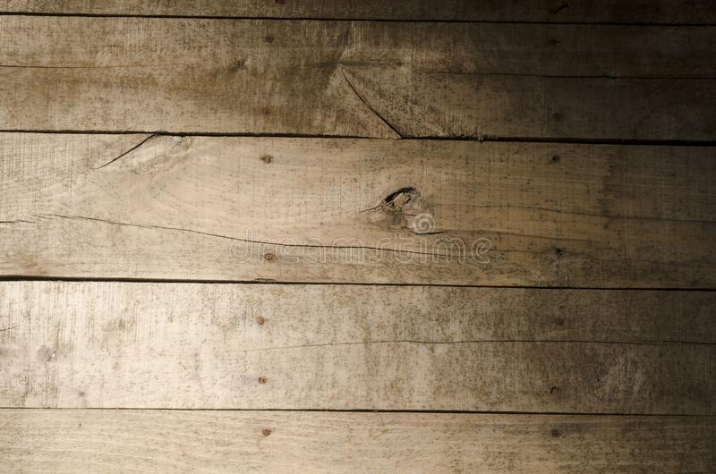 Weathered wood background. Aged wood slat wall illuminated from the left side with the right side in shadow royalty free stock images