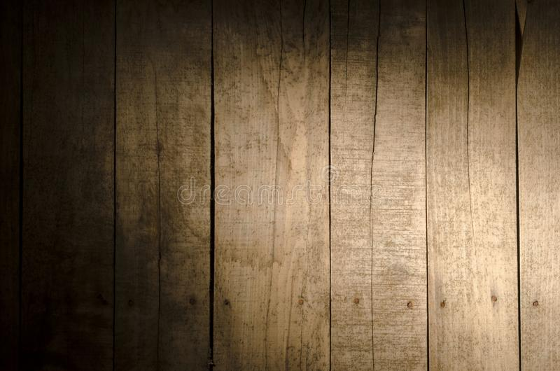 Weathered wood background. Aged wood slat wall in shadow illuminated from the right side stock image