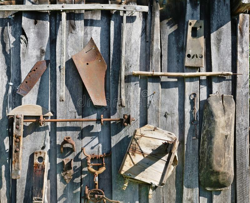 On the aged wooden l wall of the village shed barn  hang  used  old  rusty retro vintage   agricultural tool. On the aged wooden l wall of the village shed barn stock images