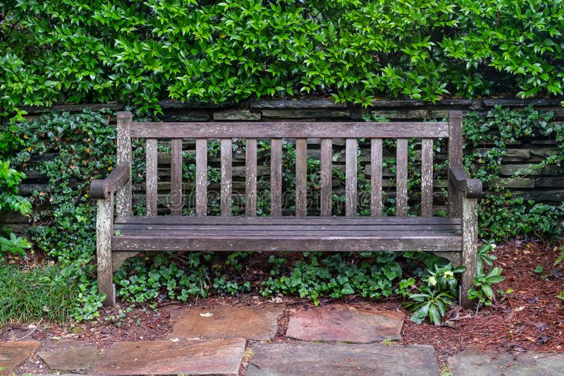Aged Wooden Park Bench on Flag Stone royalty free stock images