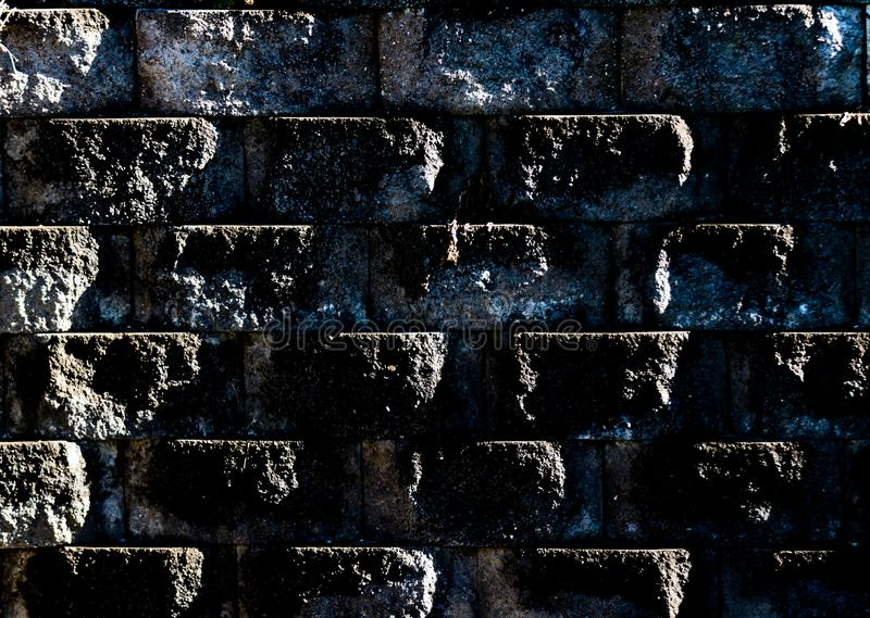 Aged worn grungy cement block wall with dirt and moss royalty free stock images