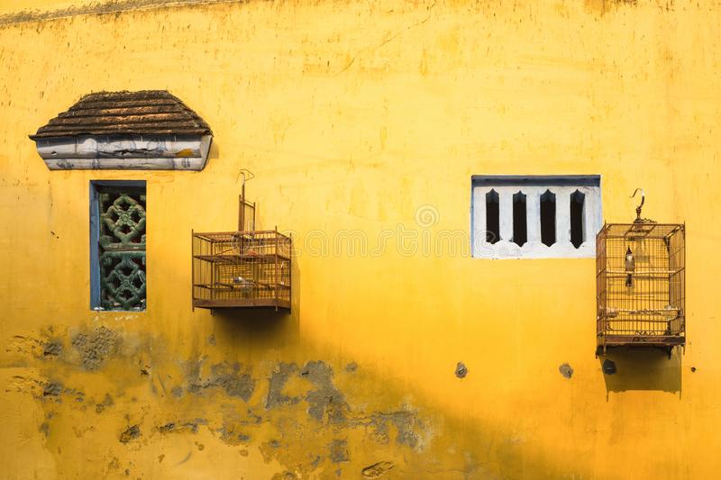 Aged yellow wall with small window and bird cage.  royalty free stock photo