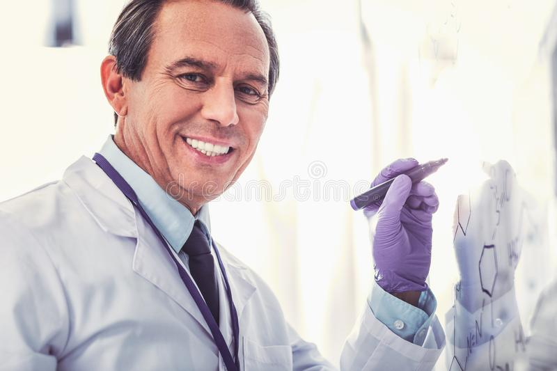 Ageing chemist wearing blue glove working. Blue glove. Ageing chemist with facial wrinkles on his face wearing blue glove feeling busy while working royalty free stock images