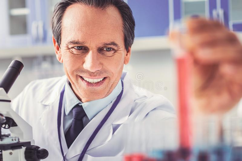 Ageing chemist with wrinkles making new report. Ageing chemist. Ageing chemist with facial wrinkles making new important monthly report stock photo