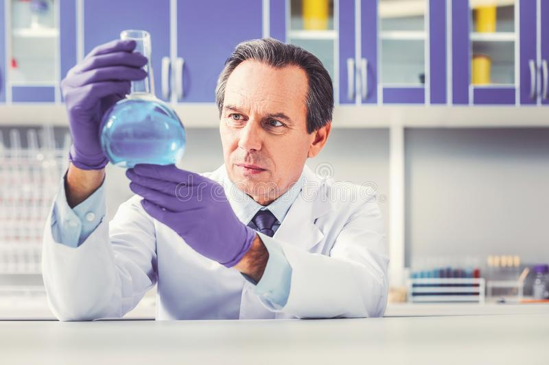 Ageing experienced chemist holding glass tube royalty free stock photos