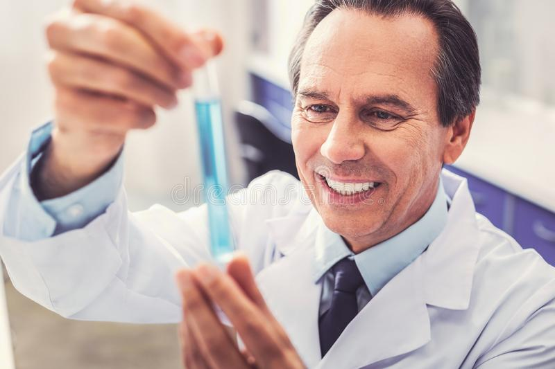 Ageing famous scientist making new research. New research. Ageing famous scientist feeling inspired while making new research in the domain of medicine stock image