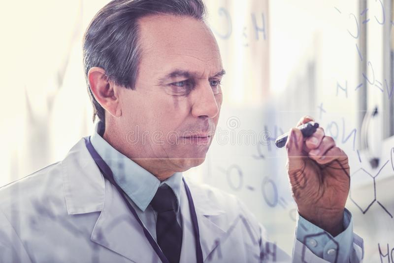 Ageing microbiologist holding marker pen writing formula. Marker pen. Ageing professional microbiologist feeling occupied while holding black marker pen writing royalty free stock image