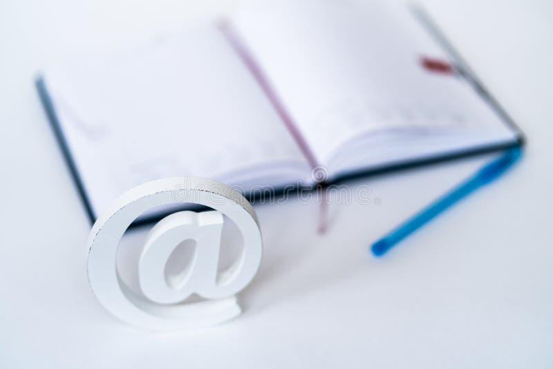 Ageinst de symbole d'email un carnet sur un bureau photo stock