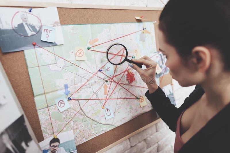 Agence de détectives privés La femme regarde la carte d'indice avec la loupe dans le bureau image libre de droits