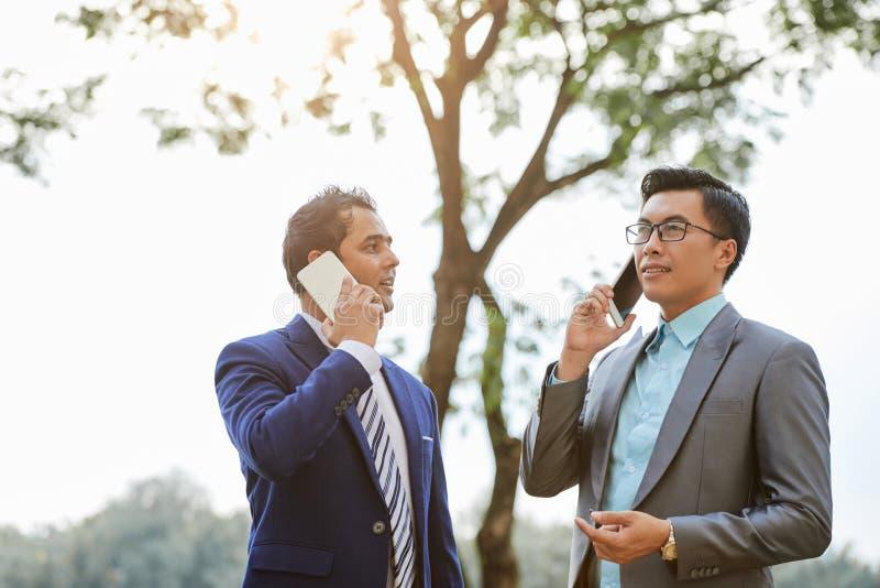 Agenci nieruchomości opowiada na telefonach obraz royalty free